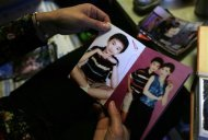 50 year-old Shi Hui shows pictures of her and her late son Tian Yao, born in August 1990 and died in January 2012 of lymphoma, at home in Beijing, December 26, 2013. REUTERS/Jason Lee