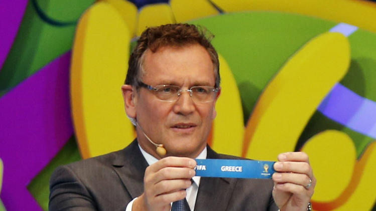 "FIFA Secretary General Jerome Valcke holds the slip showing ""Greece"" during the draw for the 2014 World Cup at the Costa do Sauipe resort in Sao Joao da Mata"