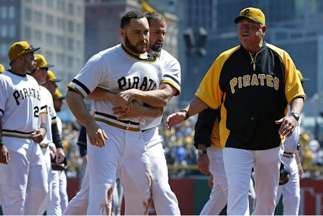 Pittsburgh Pirates' Russell Martin (55) is restrained by teammate Gaby Sanchez, center, as they walk to the dugout with manager Clint Hurdle, right, after a brawl between the Pittsburgh Pirates an