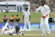 Pakistan's Asad Shafiq (L) dives to avoid a run out as Sri Lanka's Prasanna Jayawardene looks on during the fourth day of their opening Test against Sri Lanka on June 25. Shafiq and Younis Khan defied Sri Lanka during an unbroken fifth-wicket stand of 70 as Pakistan fought for survival in the first Test on Monday