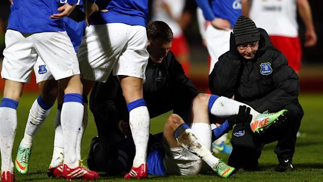 A physiotherapist holds the leg of Everton's Bryan Oviedo as he lies with a broken leg during their English FA Cup soccer match against Stevenage (Reuters)