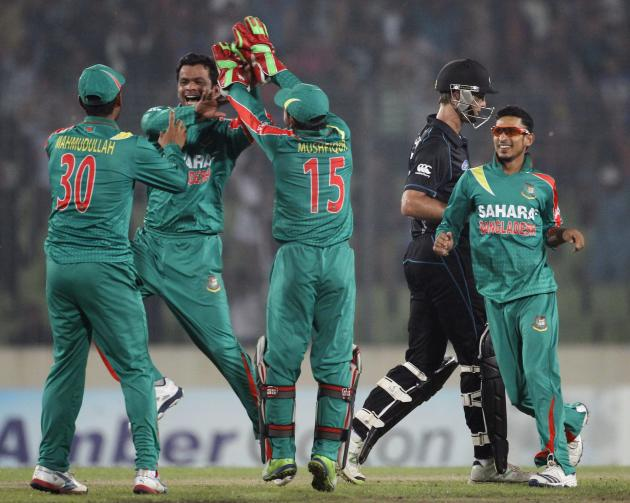 New Zealand's Grant Elliot leaves the field as Bangladesh's fielders celebrate his dismissal during their second ODI cricket match in Dhaka