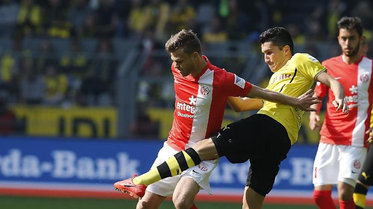 Mainz's Sebastian Polter, left, and Dortmund's Nuri Sahin of Turkey challenge for the ball during the German first division Bundesliga soccer match between BvB Borussia Dortmund and Mainz 05 in Dortmund, Germany, Saturday, April 19, 2014
