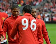 Liverpool's Uruguayan striker Luis Suarez (2nd R) shakes hands with Manchester United's Senegalese-born French defender Patrice Evra (R) and Ecuadorian midfielder Antonio Valencia (L) before the English Premier League football match between Liverpool and Manchester United at Anfield in Liverpool. United won 2-1