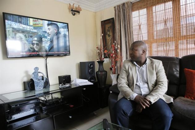 Thamsanqa Jantjie looks around at a television at his home during an interview with the Associated Press in Johannesburg, South Africa,Thursday, Dec. 12, 2013. Jantjie, the man accused of faking sign