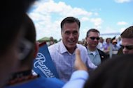 "Republican Presidential candidate, former Massachusetts Governor Mitt Romney greets people during a campaign event at Scamman Farm in Stratham, New Hampshire. Romney kicked off a six-state bus tour Friday across what he called the ""backbone of America,"" as he seeks to cast himself as more in touch with struggling voters than President Barack Obama"