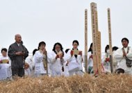 Believers pray for victims of the March 11 massive earthquake and tsunami at a memorial in Natori, Miyagi prefecture on March 8. The Red Cross warned that communities destroyed by the tsunami are years away from being righted