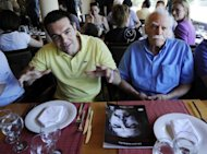 Syriza leftist radical party leader, Alexis Tsipras (L) and Greek resistance hero, politician and writer Manolis Glezos sit in a restaurant in Athens during a dinner with journalists