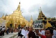Rakhine Buddhist monks and demonstrators hold banners and pictures as they gather at Yangon's Shwedagon pagoda after unrest flared in the western Myanmar state on June 10. Security forces have tried to restore order to a Myanmar state placed under emergency rule after a wave of deadly religious violence, as the United Nations evacuated foreign workers