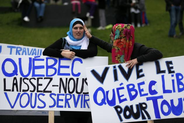 Women hold signs as they protest against Quebec's proposed Charter of Values in Montreal