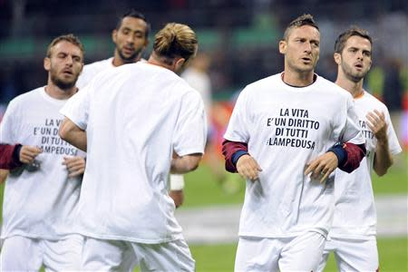 "AS Roma's Totti and team mates wear t-shirts that read ""Life it's a right for all #Lampedusa"" while warming up before their soccer match against Inter Milan in Milan"