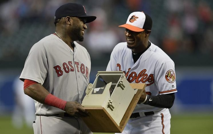 Orioles' star Adam Jones presents David Ortiz with a dugout phone, which Ortiz smashed during a game in 2013. (AP)