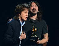 Winners for Best Rock Song Paul McCartney (L) and Dave Grohl (with Krist Novoselic and Pat Smear) give their acceptance speech on stage during the 56th Grammy Awards at the Staples Center in Los Angeles, California, January 26, 2014