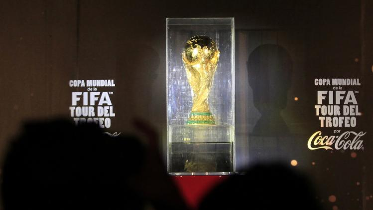Photographers take pictures of the FIFA World Cup trophy during the launch ceremony of the World Cup Trophy Tour in Mexico City