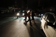 People walk on a street during a blackout in Caracas December 2, 2013. REUTERS/Carlos Garcia Rawlins