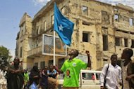 A man wearing a t-shirt with a picture of newly elected Somali President Hassan Sheikh Mohamud, waves a Somali flag as he celebrates in southern Mogadishu. The election of a new president raised hope Tuesday that Somalia could emerge from two decades of civil war, but Islamist rebels and observers reminded Hassan of the tough road ahead