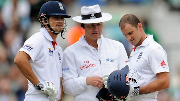 England's captain Andrew Strauss looks at the peak of his damaged helmet with teammate Alastair Cook and umpire Simon Taufel (Reuters)