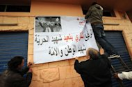 Tunisians fix a poster featuring late opposition leader Chokri Belaid during his funeral procession Djebel Jelloud district of Tunis, on February 8, 2013. Tunisian police have fired tear gas and clashed with protesters as tens of thousands joined the funeral of Belaid whose murder plunged the country into new post-revolt turmoil