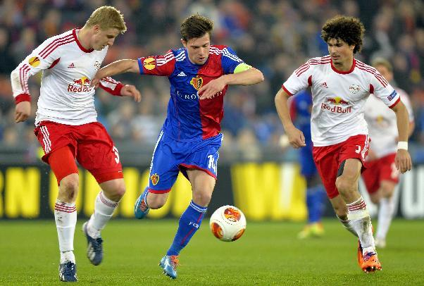 Basel's Valentin Stocker, center, is challenged by Salzburg's Martin Hinteregger, left, and Andre Ramalho during the Europa League round of sixteen first leg soccer match between Switzerland&#