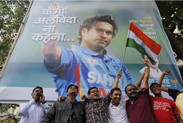 Cricket fans holding an Indian national flag shout slogans in front of a billboard of cricketer Sachin Tendulkar outside a stadium in Mumbai