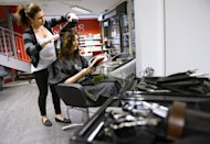 A hairdresser styles a woman's hair at a salon in Stockholm, Sweden on June 12, 2013. Twenty years after Sweden's school system opened the door for independent profit-making schools and expanded parents' choice, sliding results have the leftist opposition saying the system is a textbook example of privatisation gone wrong