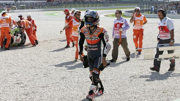 Honda MotoGP rider Dani Pedrosa leaves track after crash with Ducati's Hector Barbera during San Marino Grand Prix