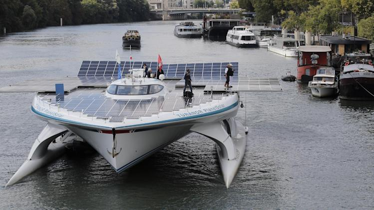 The Turanor PlanetSolar, the world's largest solar boat, travels on the Seine river in Paris, Tuesday, Sept. 10, 2013. The PlanetSolar with its 537 square meters of photovoltaic panels powering 6 blocks of lithium-ion batteries, accomplished the first around the world trip powered only by solar energy in May 2012. (AP Photo/Christophe Ena)