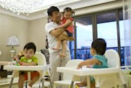 Tony Jiang poses with his three children at his house in Shanghai, September 16, 2013. REUTERS/Aly Song