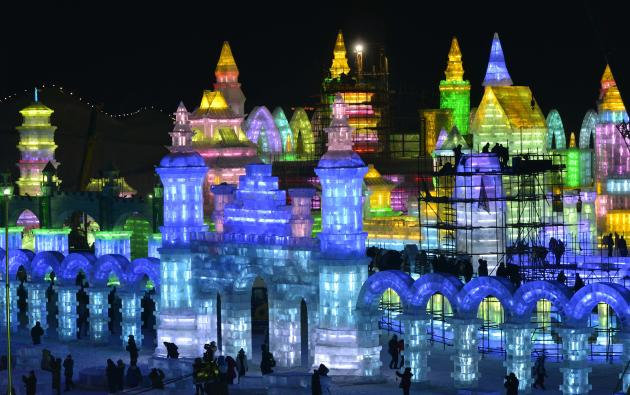 Workers and scaffoldings are seen next to newly-built ice sculptures illuminated by coloured lights ahead of the 30th Harbin Ice and Snow Festival, in Harbin