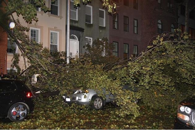 A fallen tree branch sits on a car blocking East 74th St. between Lexington Avenue and Third Avenue on Manhattan's Upper West Side on Monday, Oct. 29, 2012. Sandy made landfall Monday night, hurling a