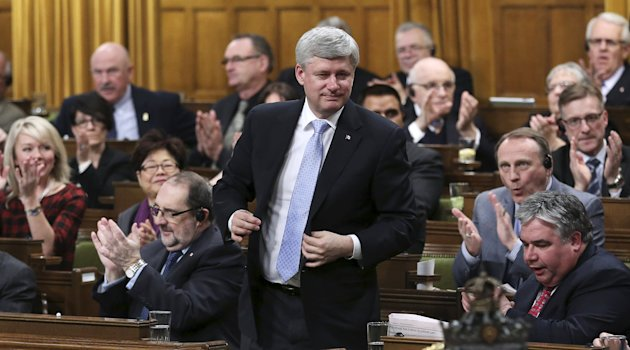 Canada's Prime Minister Stephen Harper stands to vote in the House of Commons on Parliament Hill in Ottawa March 30, 2015. Parliamentarians voted to expand Canada's military mission against Islamic State by launching air strikes against the militants' safe havens in Syria as well as Iraq. REUTERS/Chris Wattie
