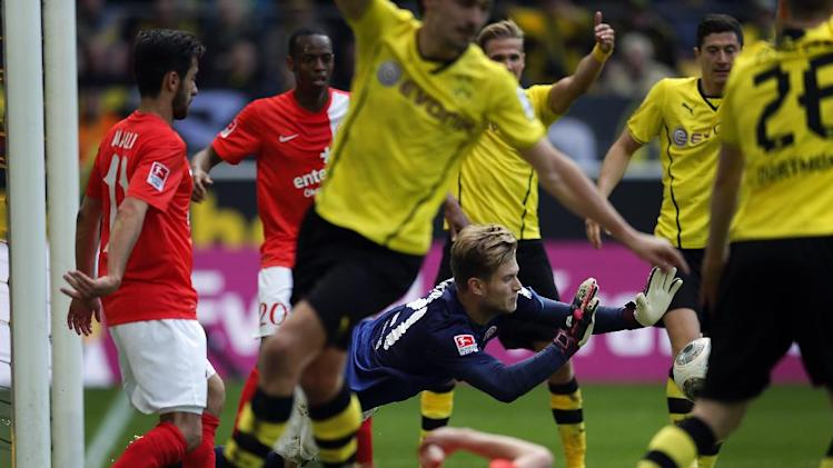 Mainz goalkeeper Loris Karius, center in blue, jumps for the ball during the German first division Bundesliga soccer match between BvB Borussia Dortmund and Mainz 05 in Dortmund, Germany, Saturday, April 19, 2014