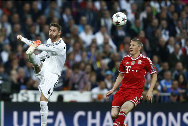 Real's Sergio Ramos kicks the ball next to Bayern's Bastian Schweinsteiger, right, during a first leg semifinal Champions League soccer match between Real Madrid and Bayern Munich at the Santi