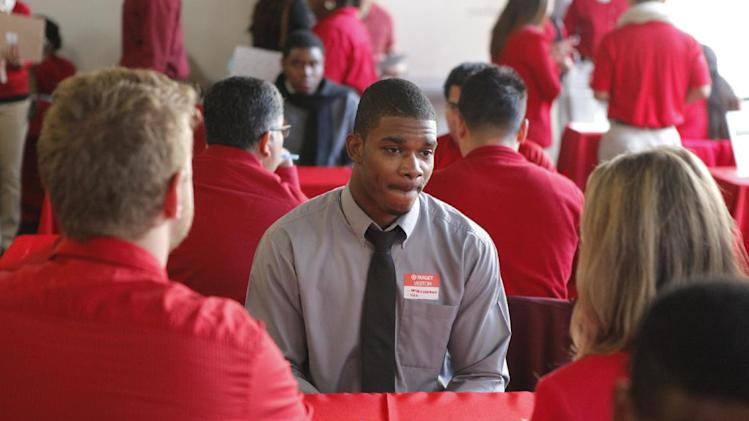 In this Thursday, Jan. 10. 2013, photo, Business management student Matthew Brathwaite, 22, originally from Jamaica, middle, applies for a overnight logistics position at a Target job fair in Los Angeles. The number of Americans seeking unemployment benefits fell last week to the lowest level in five years, a positive sign that layoffs have fallen and hiring may pick up. (AP Photo/Damian Dovarganes)
