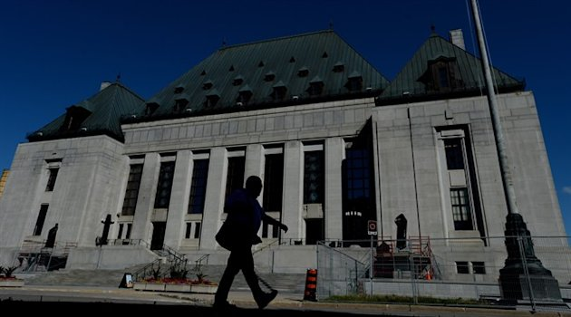 A pedestrian walks past the Supreme Court of Canada in Ottawa on Thursday, July 23, 2015. THE CANADIAN PRESS/Sean Kilpatrick