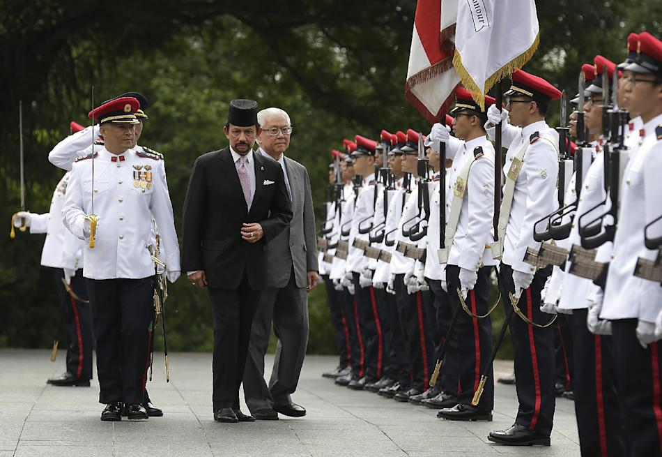 Brunei Sultan Hassanal Bolkiah, center, accompanied by Singapore's President Tony Tan, center right, inspects a guard of honor during a welcome ceremony Monday, April 21, 2014 at the Istana or Pre