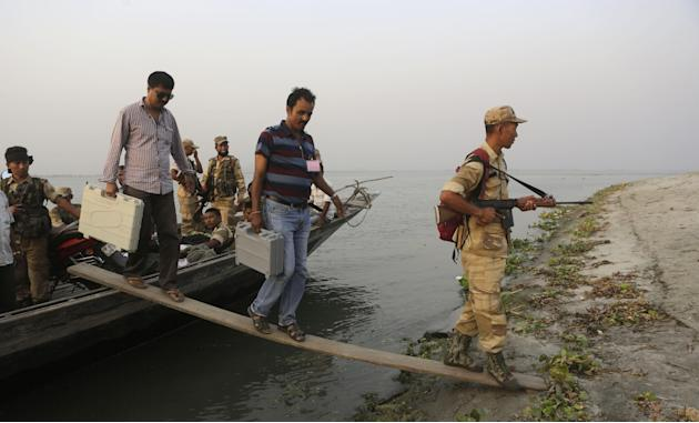 Election officers alight from a boat carrying electronic voting machines, guarded by security personnel as they travel to their assigned polling stations on the eve of voting near Kalapani village, ab