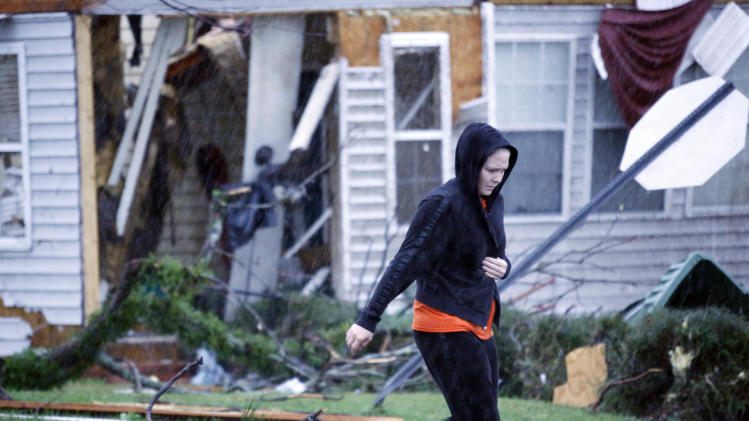 Amy McQueen, 28 rushes to her brother's house Monday, Feb. 11, 2013 to help him remove the his belongings after is was destroyed by Sunday's tornado in Hattiesburg, Miss. (AP Photo/Rogelio V. Solis)