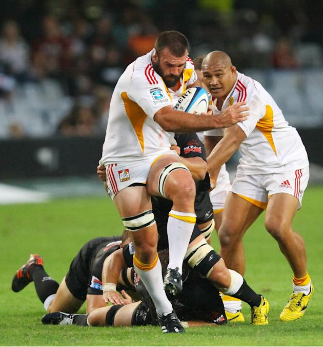 New Zealand Waikato Chiefs' Alex Bradley (C) breaks away from Durban Sharks' defence during a Super 15 rugby union match at the Mr Price Kings Park Rugby Stadium on April 21, 2012.  AFP PHOTO (Photo c
