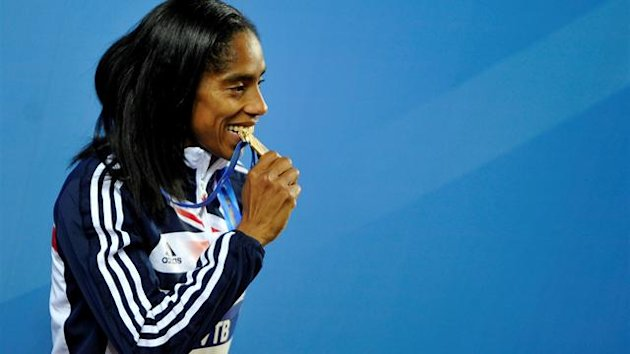 Yamile Aldama of Britain bites her gold medal during the awards ceremony for the women's Triple Jump at the world indoor athletics championships at the Atakoy Athletics Arena in Istanbul