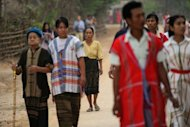 Residents walk to a polling station in Kawhmu, the constituency where Myanmar opposition leader Aung San Suu Kyi is standing on April 1, 2012