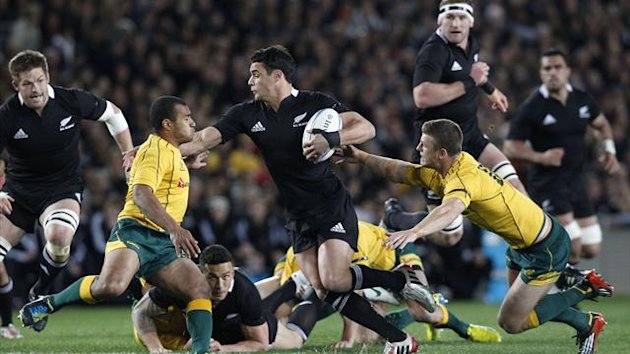 Dan Carter of New Zealand's All Blacks tries to avoid being tackled by Will Genia (L) and Rob Horne (R) of Australia