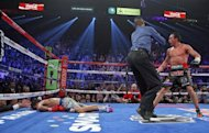 Referee Kenny Bayless (C) holds back Juan Manuel Marquez (R) as Manny Pacquiao lies face down on the canvas after being knocked out on December 8 at the MGM Grand Garden in Las Vegas. Philippine media commentators have put pressure on their national icon to now retire