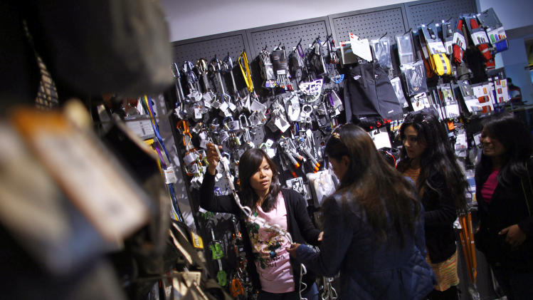 In this Tuesday, Feb. 21, 2013 photo, Nepalese climber Asha Singh, center, looks at climbing gear at a store in Katmandu, Nepal. Aiming to change the all-male image of mountaineering in the country, a group of Nepalese women have embarked on a mission to climb the tallest mountain on each of the seven continents. The women, aged between 21 and 32, have already climbed Everest in Asia, Kosciuszko in Australia and Elbrus in Europe and are preparing next week to climb Mount Kilimanjaro in Africa to mark International Women's Day. (AP Photo/Niranjan Shrestha)