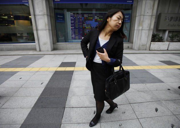 A woman walks by an electric stock board outside a securities firm, Friday, April 18, 2014 in Tokyo. Asian stocks were mostly higher Friday after mixed U.S. earnings reports with most of the region's