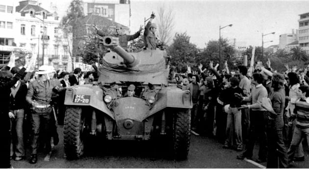 FILE - In this April 25 1974 file picture, people cheer soldiers in a tank driving through downtown Lisbon during a military coup. Euphoria gripped Portugal during the 1974 Carnation Revolution, when