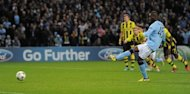 Manchester City's Italian forward Mario Balotelli (R) scores from a penalty during the UEFA Champions League football match between Manchester City and Borussia Dortmund at the Etihad stadium, in Manchester. The match ended in a 1-1 draw