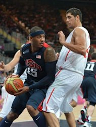 US forward Carmelo Anthony (L) vies with Tunisian forward Mohamed Hadidane during the Men's preliminary round group A basketball match of the London 2012 Olympic Games Tunisia vs USA at the basketball arena in London. USA won 110 to 63