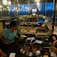 Costumers are being served by a robot at the Hajime restaurant in Bangkok on June 19, 2013. Two large robots wheel up and down the tables delivering meals to diners