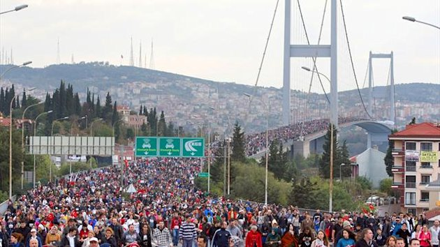 People walk over the Bosphorus Bridge that links Istanbul's European and Asian side during the 34th annual Euroasia Marathon and People's Run in Istanbul on November 11, 2012.